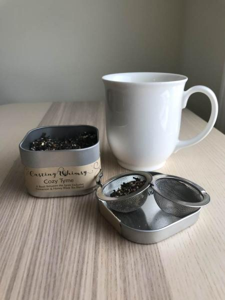 Cozy Tyme Tea container is open on a light wood table, a white mug is to the right and a tea strainer filled with tea in the foreground
